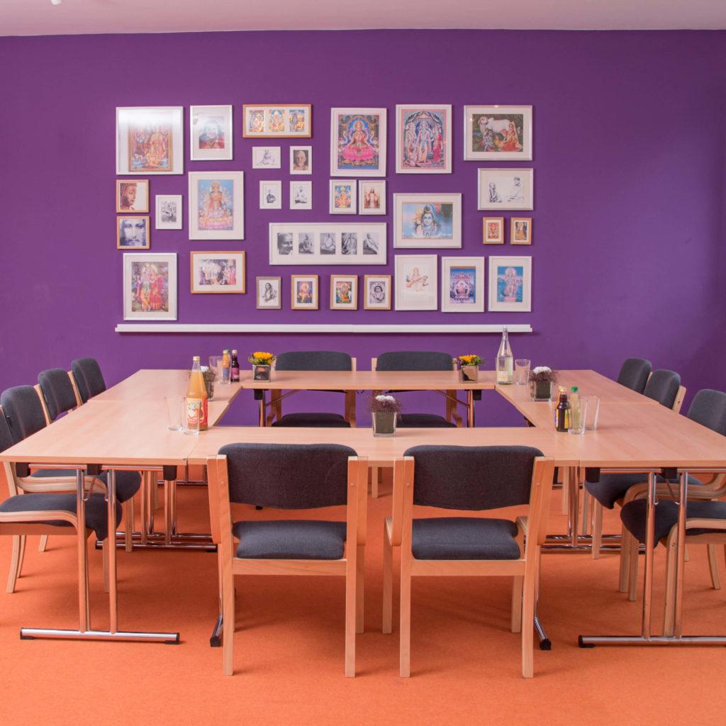 Konferenzsraum in Kreis Form mit Getränken, lila Wand und Bildern