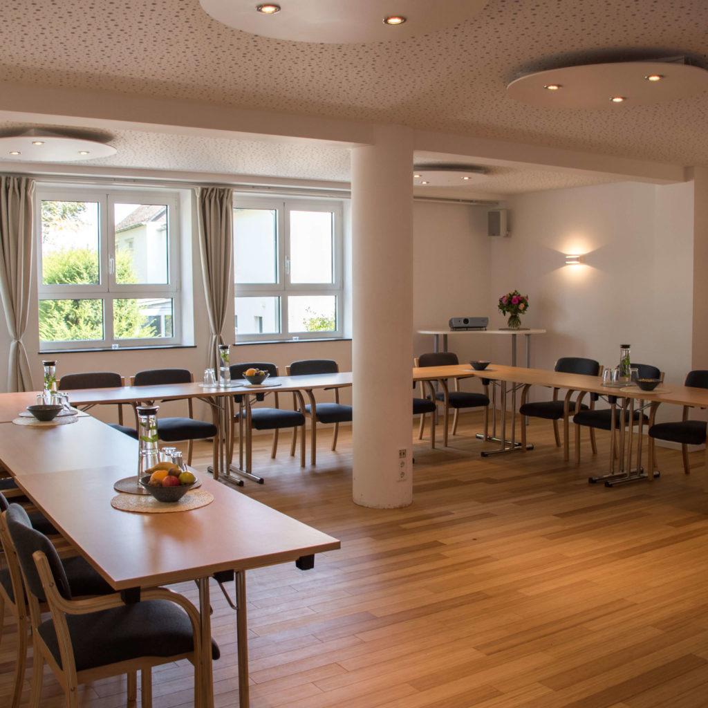 Konferenzraum in großer U-Form mit Säule in der Mitte und Tagungsverpflegung