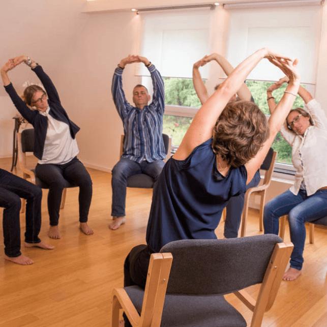 Mehrere Personen im Kreis sitzend machen verschiedene Dehnübungen
