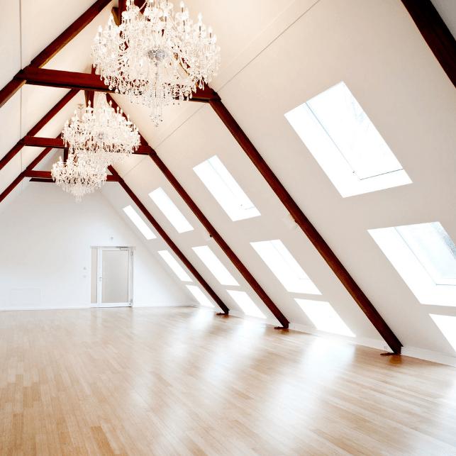 Tagungsraum leer mit Dachbalken und Kronleuchtern.