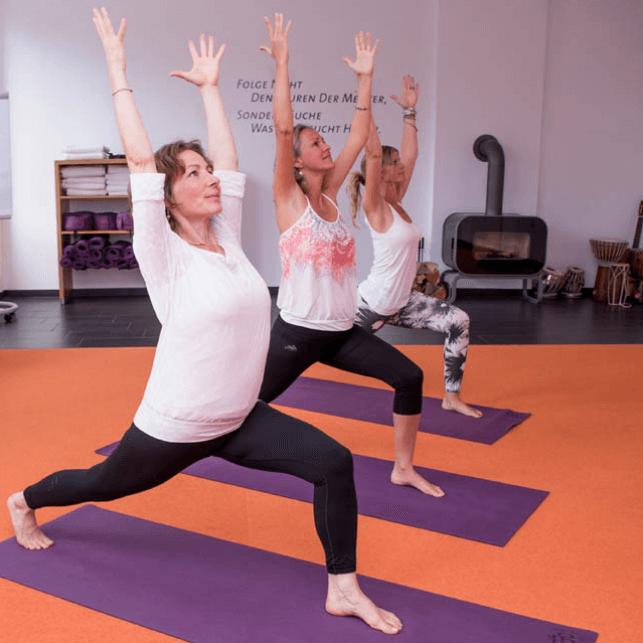 Yoga im Tagungsraum auf lila Yogamatten